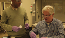 Mike Crawford of Dupont (right) and Souleymane Diallo, instrument scientist for the Backscattering Spectrometer at SNS, prepare a material sample for an experiment on the instrument.